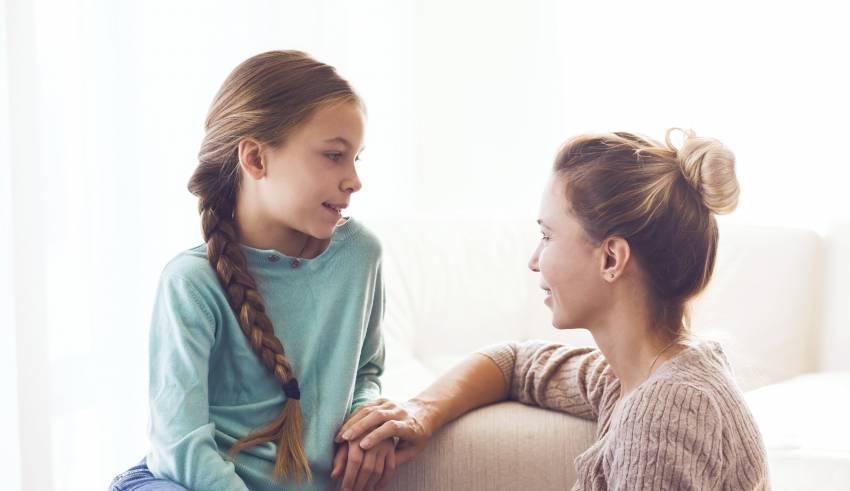 Madre e hija conversando sobre los cambios producto de la pubertad.